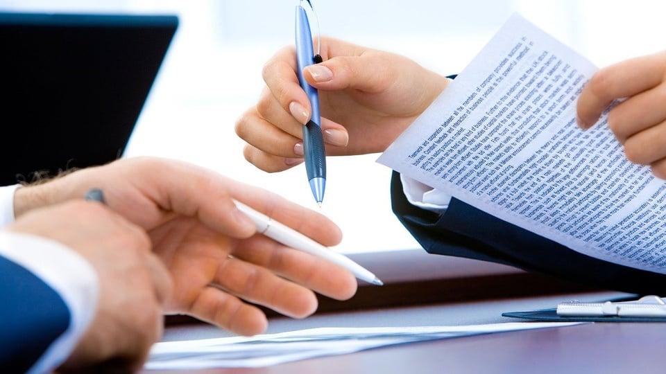 Prefeitura de Águas Frias: a imagem mostra mãos de pessoas sentadas em lados opostos de uma mesa segurando canetas e papéis