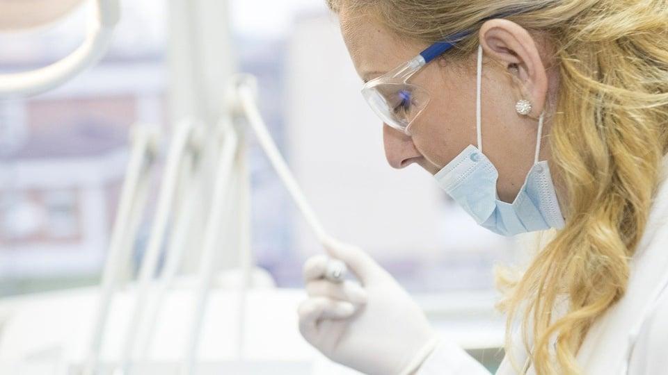 Processo seletivo Prefeitura de Alto Paraíso: mulher, profissional de saúde, de máscara, óculos e luvas realizando procedimento