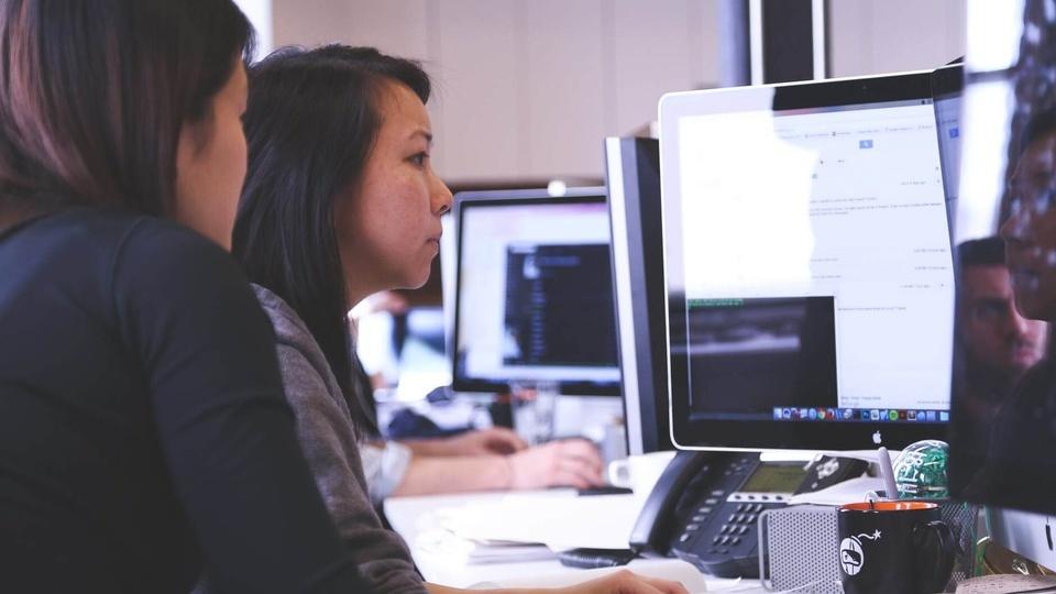Prefeitura de Anchieta: a foto mostra duas mulheres visualizando a tela de um computador de mesa
