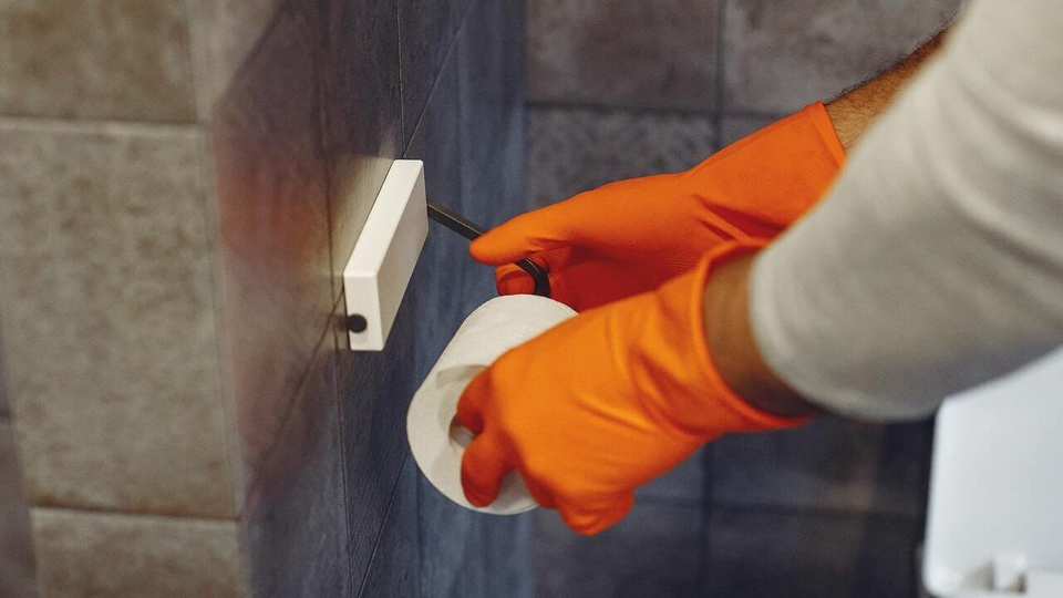 Prefeitura de Belém - PA: imagem de uma mão com luva pegando em um rolo de papel higiênico em um banheiro