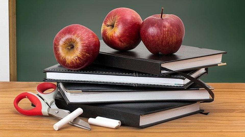 Prefeitura de Benjamin Constant: sobre uma mesa há uma tesoura, giz, agendas e maçãs. Ao fundo, é possível ver um quadro negro.