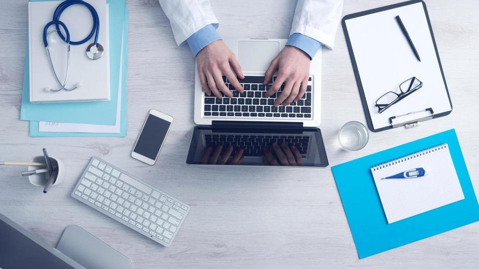 Prefeitura de Buritis - RO: foto de um médico em sua mesa com diversos equipamentos: estetoscópio, notebook, celular, prancheta, caneta, termômetro, óculos e canetas.