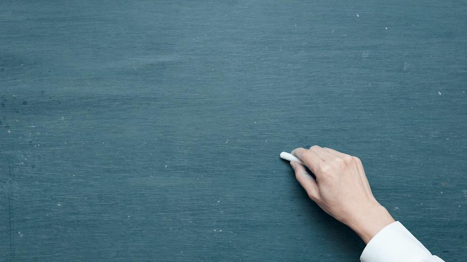 Processo seletivo Prefeitura de Caxambu do Sul: foto de uma mão com um giz escrevendo em uma lousa