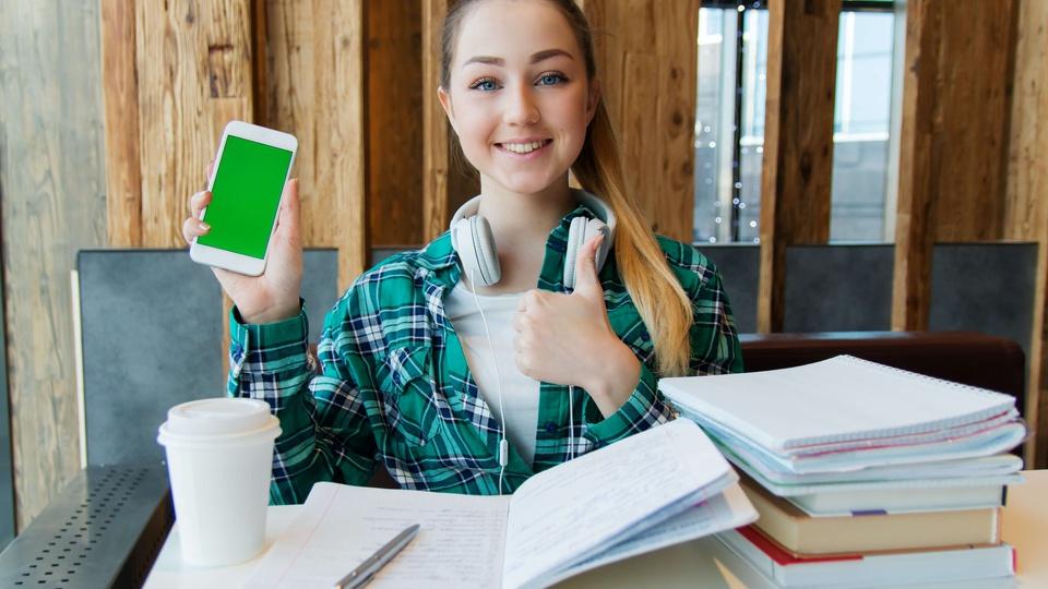 """Prefeitura de Confresa: a foto mostra uma estudante com fone de ouvido pendurado no pescoço, exibindo a tela verde de um celular e com a outra mão acenando o sinal de """"joinha"""". Em sua mesa livros, cadernos, caneta e copo"""