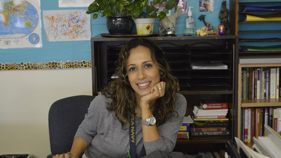 Chamada pública Prefeitura de Correia Pinto - SC: mulher sentada em cadeira, em frente a uma mesa; ao fundo uma estante com livros