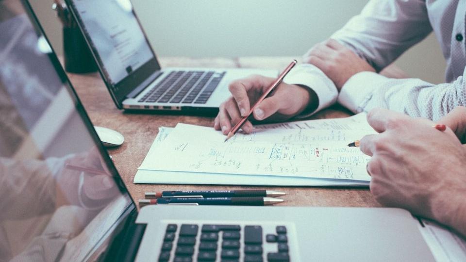 prefeitura de costa marques ro: a foto mostra pessoa com caneta na mão, fazendo anotações, uma mesa com dois notebooks e duas lapiseiras de grafite