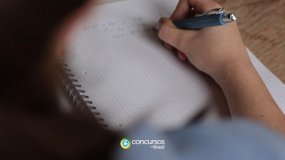 Prefeitura de Cruzeiro do Sul - AC: a imagem mostra uma mão segurando uma caneta anotando em um caderno