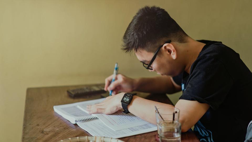 Prefeitura de Cunhataí - SC: homem escrevendo em caderno sobre mesa