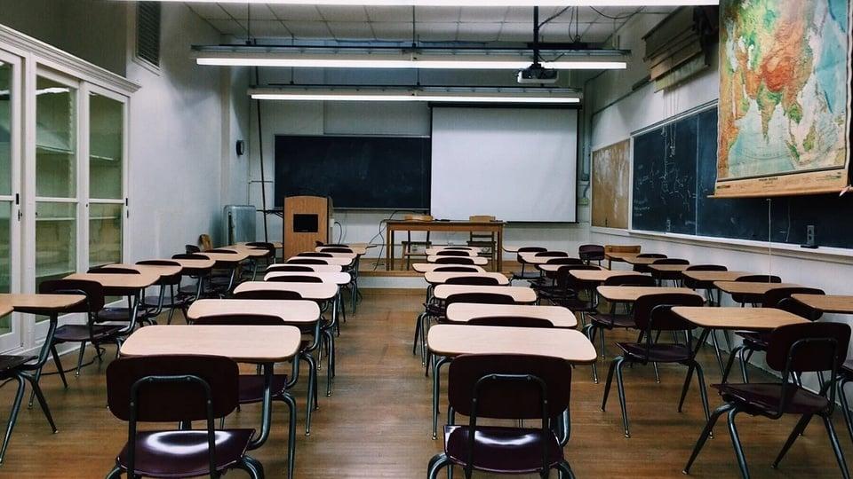 Prefeitura de Curralinhos PI: #PraCegoVer sala de aula com várias carteiras, quadro branco e quadro verde, sem nenhuma pessoa presente, o piso amadeirado