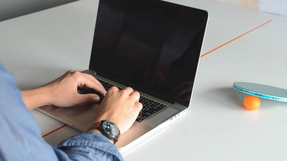 Processo seletivo Prefeitura de Curvelo - MG: mesa com notebook sob ela; homem está com as mãos em cima do teclado do notebook