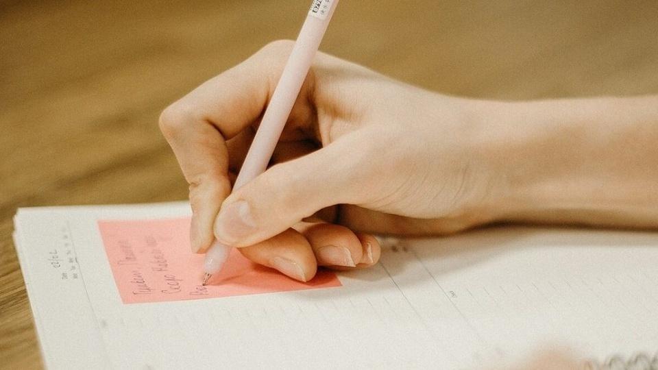 Prefeitura de Descanso: mão escrevendo algo em post-it cor-de-rosa colado em caderno