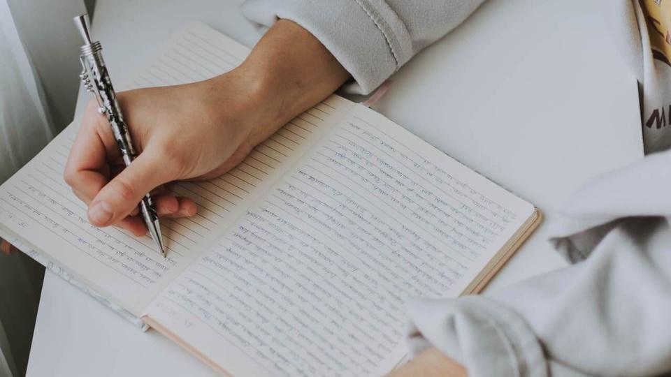 Concurso Prefeitura de Presidente Epitácio - SP: imagem de uma pessoa escrevendo em um caderno