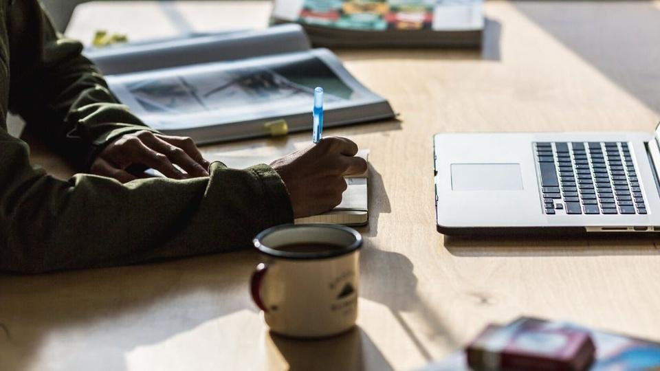 Processo seletivo Prefeitura de Formosa do Sul - SC: a foto mostra pessoa escrevendo em um caderno, uma mesa com uma xícara cheia de café ou chá, um notebook e outros objetos