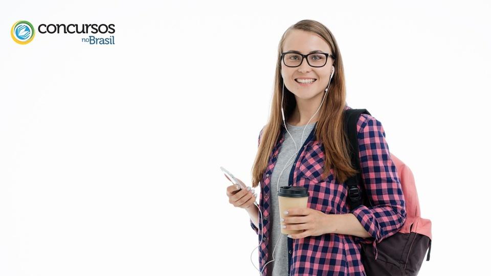 Prefeitura de Franca - SP abre vagas de estágio: estudante mulher, com óculos, usando fone de ouvido, com um copo descartável de café em uma mão e o celular em outra, sorridente