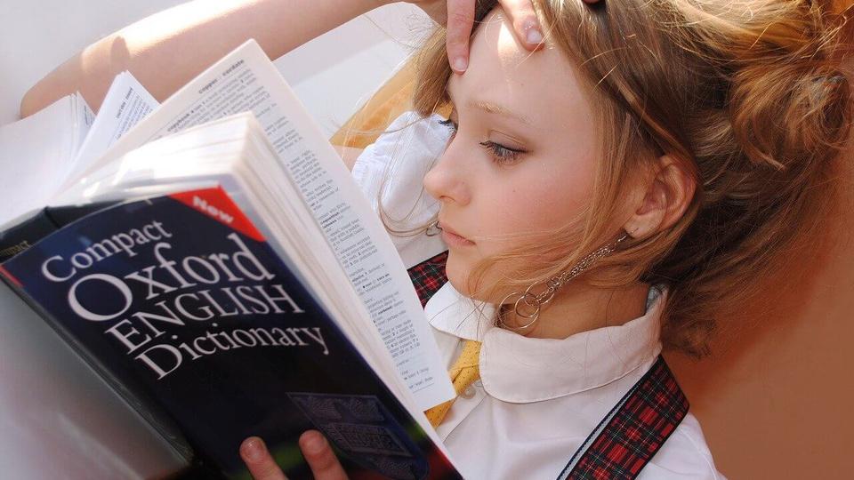 Prefeitura de Guararema: a foto mostra uma jovem loira de óculos lendo em um dicionário de inglês chamado Oxford English Dictionary