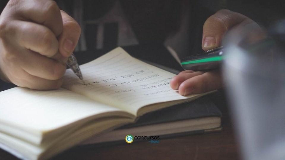 prefeitura de guaruja do sul: foco em pessoa escrevendo em caderno e com celular na mão; embaixo e centralizado a logomarca do Concursos no Brasil