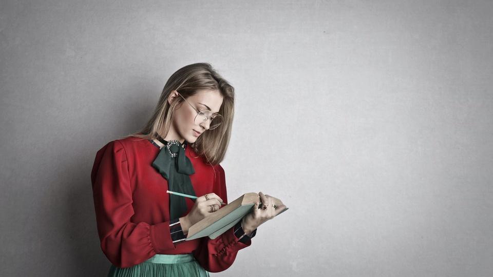 Prefeitura de Ipanguaçu: a foto mostra mulher de pé com livro e lápis nas mãos