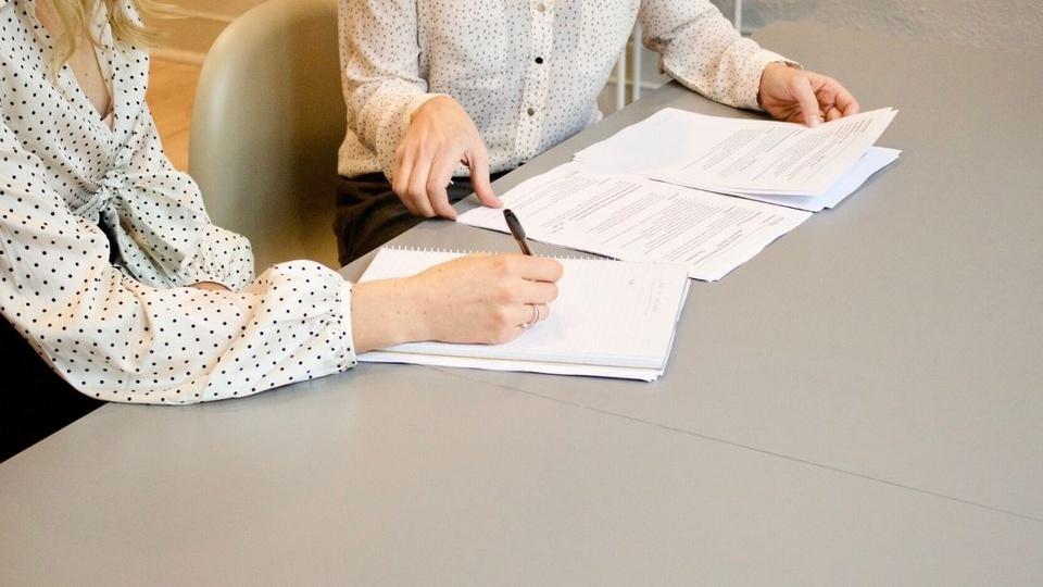Processo seletivo Prefeitura de Ipira - SC: folhas sobre a mesa, pessoa escrevendo em folha de papel