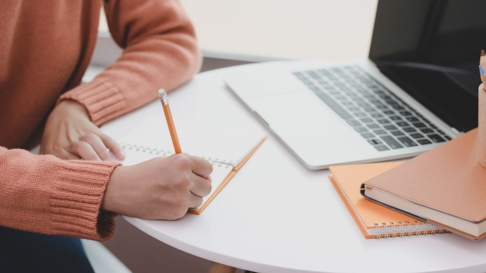 Prefeitura de Ipiaçu - foto mostra pessoa estudando com livros e notebok sobre mesa