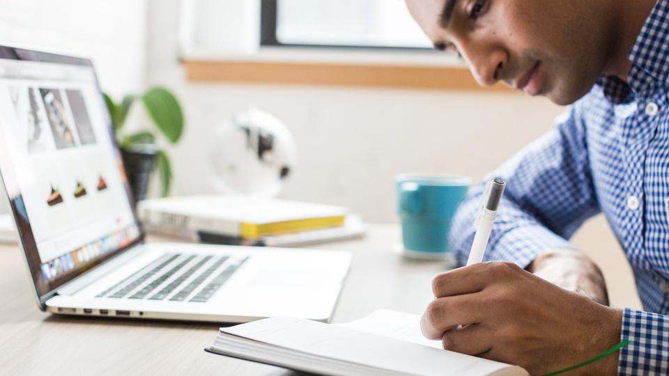 Prefeitura de Itapuã do Oeste - foto mostra homem vestido em camisa de manga longa na cor azul, sentado à mesa enquanto estuda com caderno na mão e notebook em sua frente
