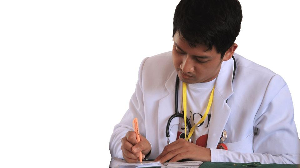 Processo seletivo Prefeitura de Itaquitinga - PE: profissional médico escrevendo, com estetoscópio pendurado no pescoço e vestindo jaleco branco