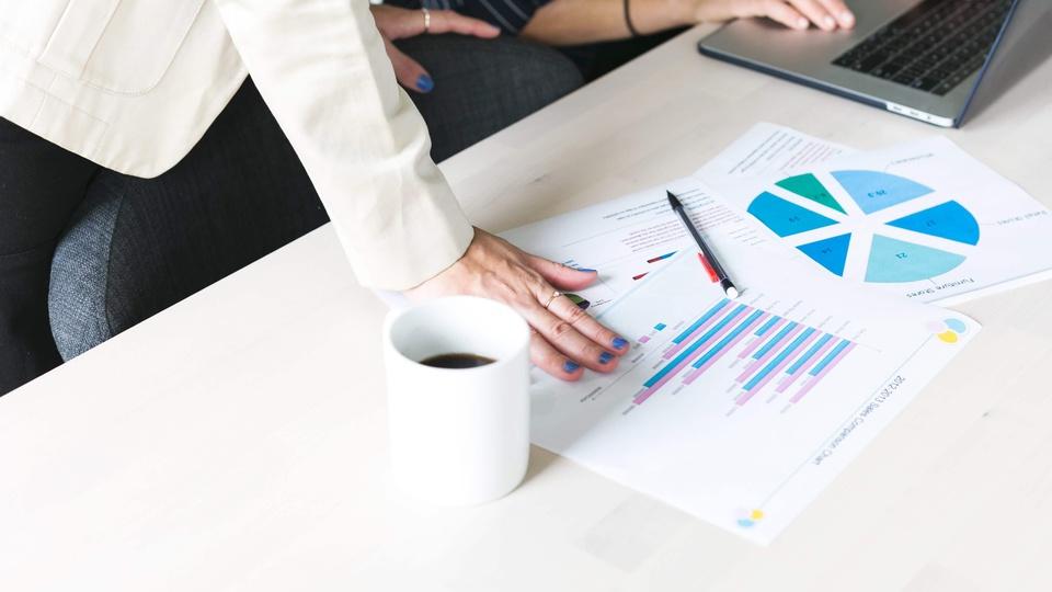 Concurso Prefeitura e Câmara de Itauçu - GO: a foto mostra duas pessoas diante de uma mesa com papéis, xícara de café, caneta e notebook