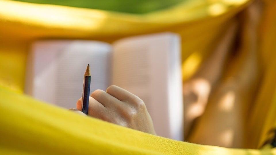 Prefeitura de Lagoa Grande: pessoa deitada numa rede amarela segura um livro e um lápis