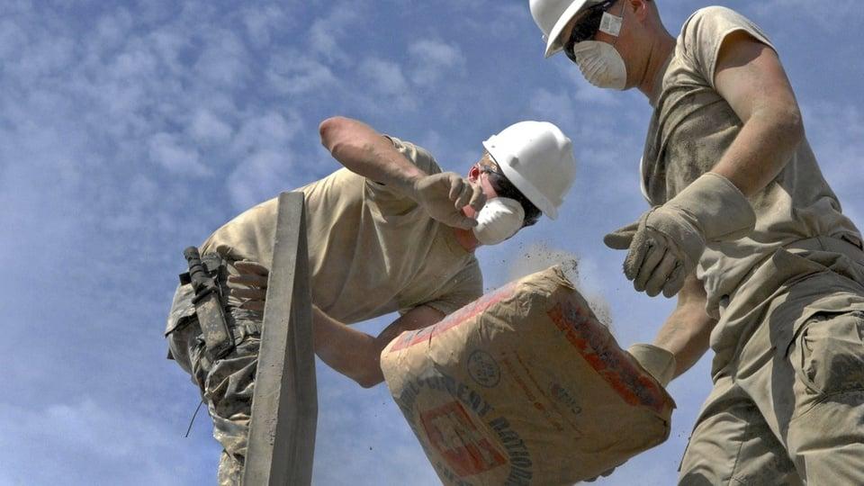 Prefeitura de Malta: pedreiros jogando um saco de cimento