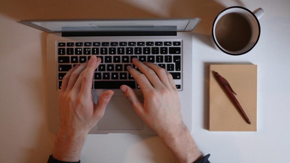 Processo seletivo Prefeitura de Maracajá - SC: foco em mãos digitando em teclado de notebook