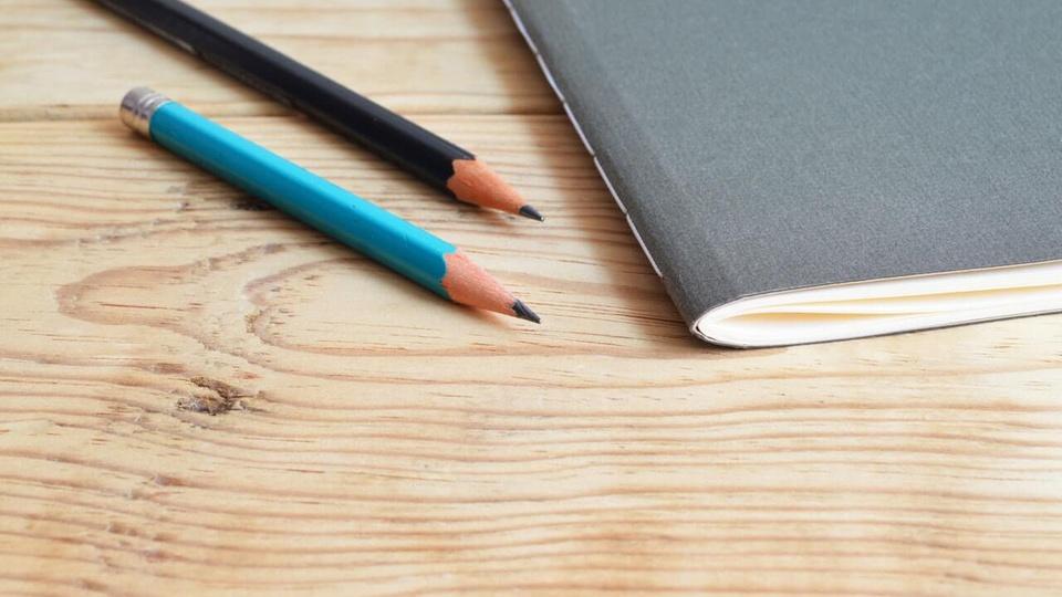 Processo seletivo Prefeitura de Mondaí - SC: foto mostra caderno e dois lápis em cima de uma mesa de madeira