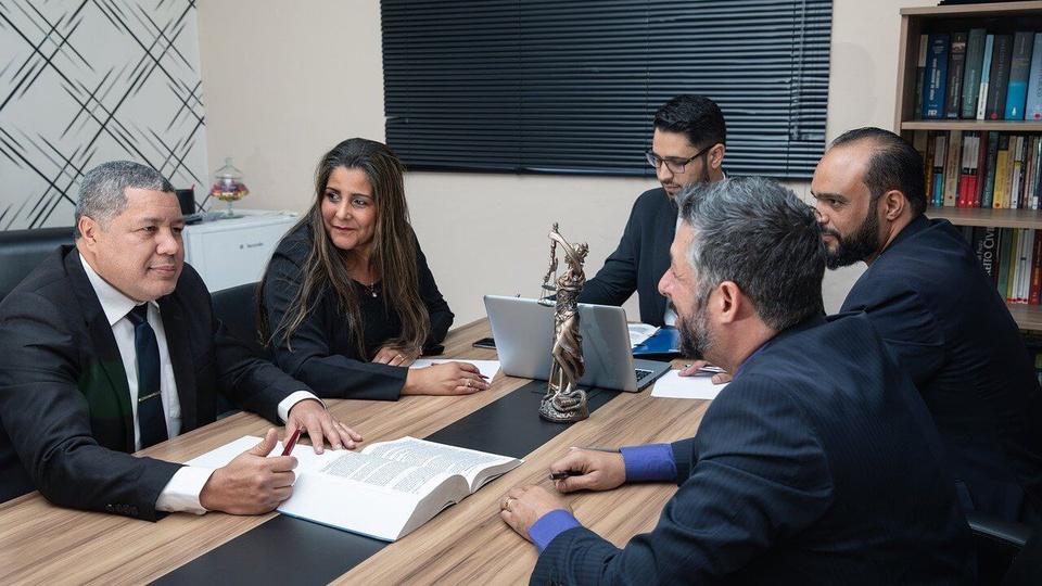 concurso Prefeitura de Monte Azul Paulista: a foto mostra cinco pessoas participando de uma reunião, há um livro aberto sobre a mesa e alguém utiliza um notebook