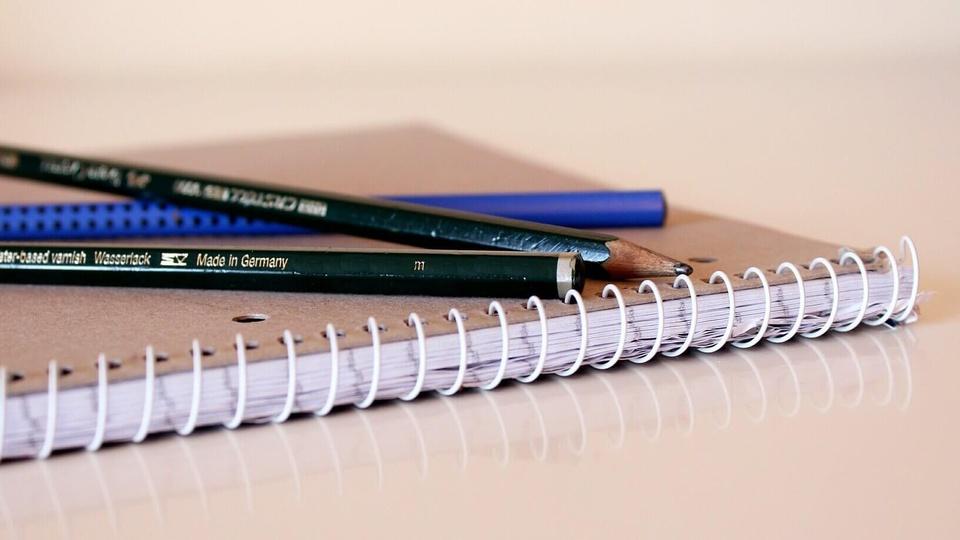 Processo seletivo Prefeitura de Muriaé: caderninho de capa cor-de-rosa com duas canetas em cima