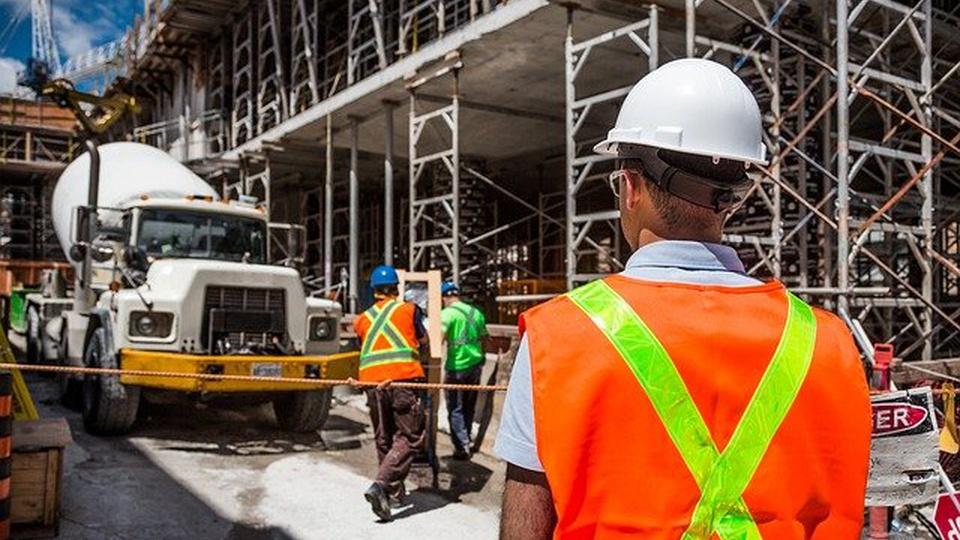 Prefeitura de Não-Me-Toque: imagem de uma construção. Na foto aparece um caminhão e um profissional com equipamento de proteção individual (EPI)