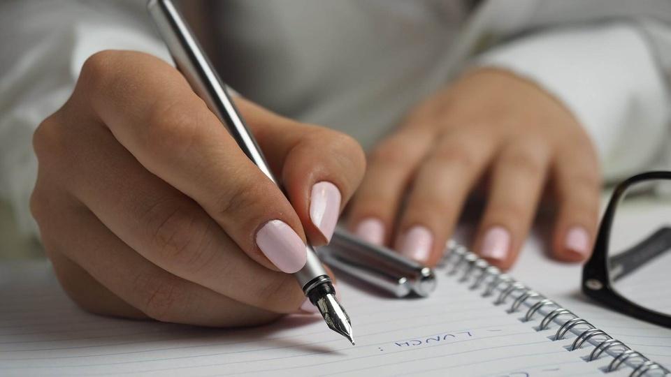 Processo seletivo Prefeitura de Nova Trento - SC: mulher escrevendo em folha de papel