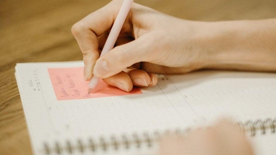 Prefeitura de Nova Veneza - SC: enquadramento fechado em mão escrevendo com uma caneta num post-it colado num caderno