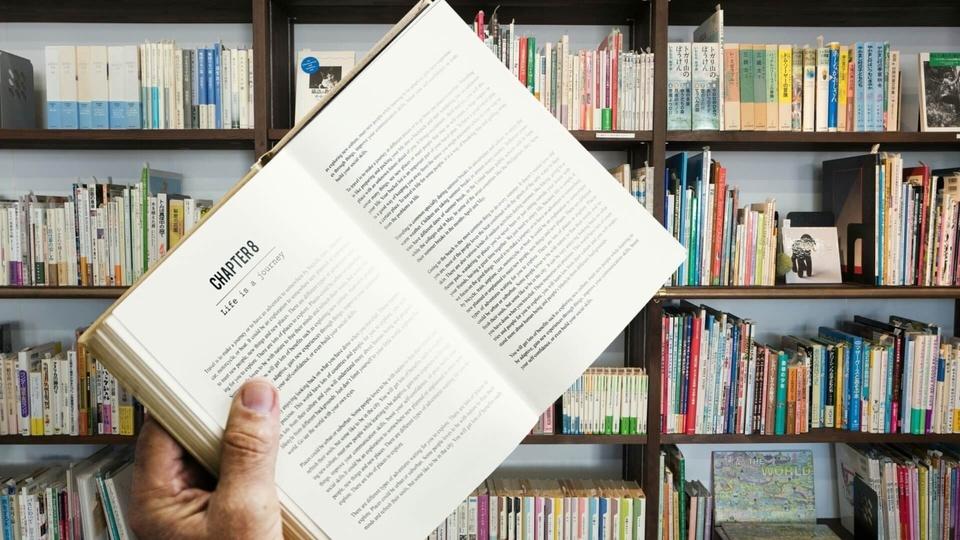 Processo seletivo Prefeitura de Novo Cabrais - RS: pessoa segundo livro, ao fundo uma estante cheia de livros