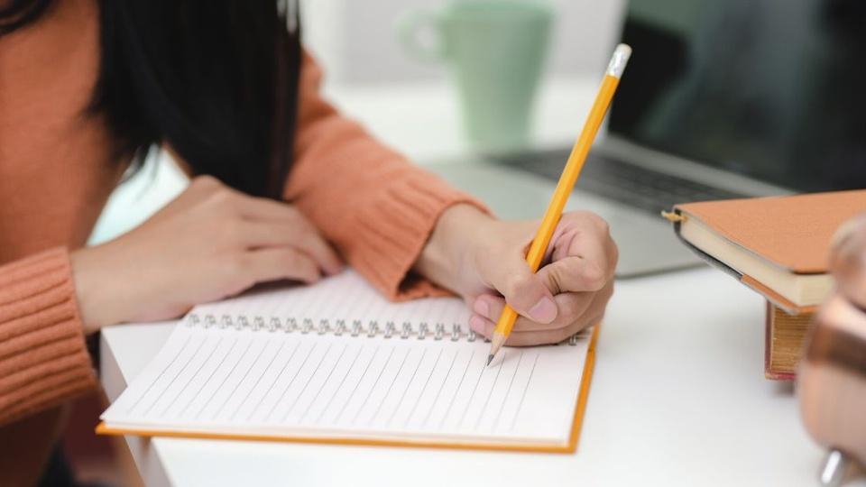 Prefeitura de Novo Horizonte do Oeste - plano fechado em braço de pessoa com roupa de manga longa escrevendo em caderno com lápis