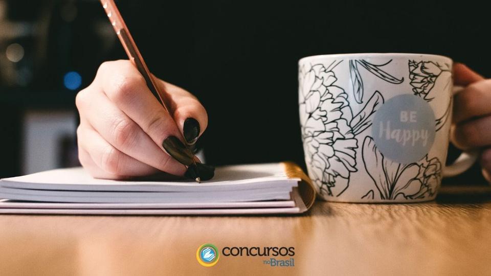 Prefeitura de Novo Mundo: mulher escrevendo algo em um caderno, ao lado do caderno tem uma xícara. Abaixo, o logotipo do site Concursos no Brasil.