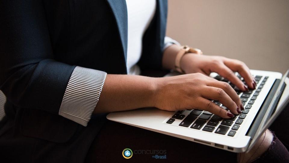 prefeitura de ouro preto: a foto mostra uma mulher bem vestida utilizando um notebook em seu colo, digitando