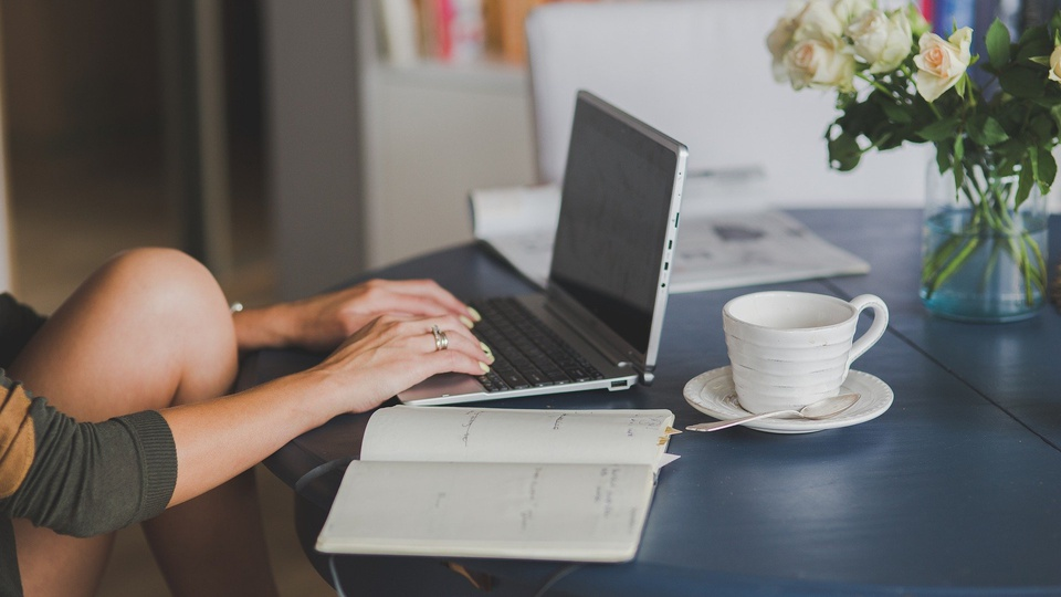 Processo seletivo Prefeitura de  Paranaíta - MT: a foto mostra pessoa estudando com livro, notebook e uma xícara sobre a mesa