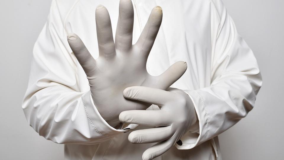 Processo seletivo Prefeitura de Paulista - PE: pessoa usando jaleco branco e luxas cirúrgicas brancas com a mão aberta à frente