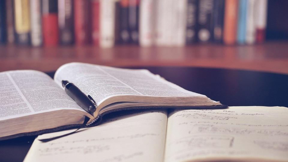 Prefeitura de Peixoto do Azevedo: livros e caneta em cima de uma mesa. Ao fundo, fora de foco, é possível ver uma estante de livros