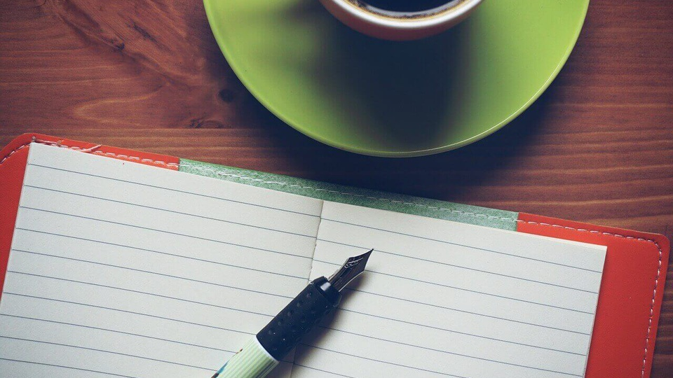 processo seletivo Prefeitura de Perdigão: a imagem mostra caderno aberto com caneta em cima em frente xícara de café
