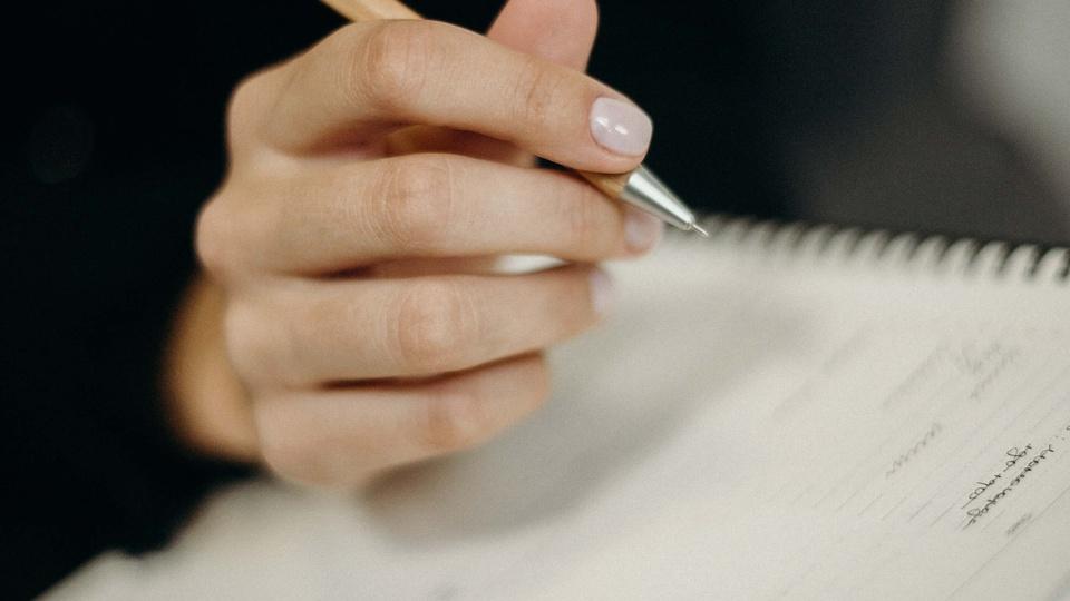 Prefeitura de Pimenta Bueno: mão de uma pessoa segurando uma caneta e escrevendo em um caderno.