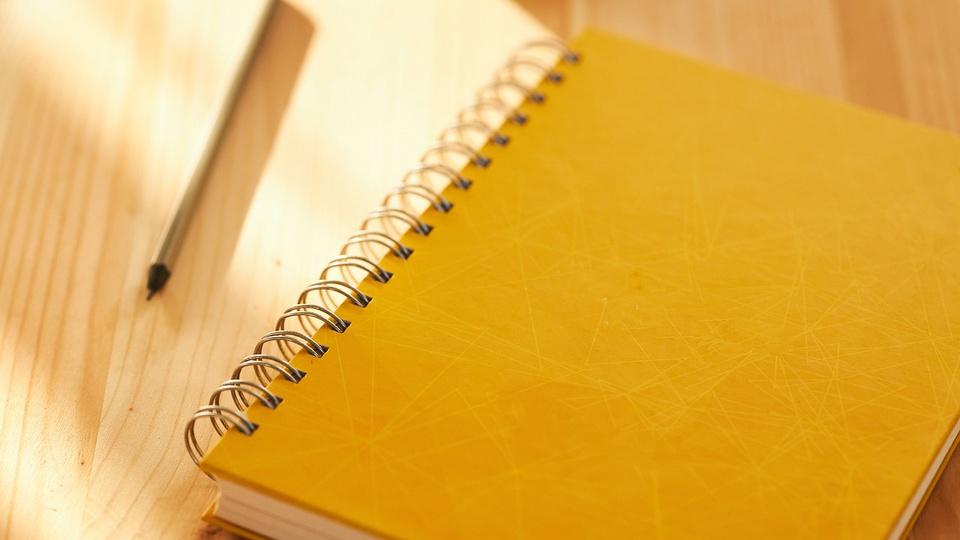 Prefeitura de Piúma: a imagem mostra caderno de capa amarela ao lado de lápis