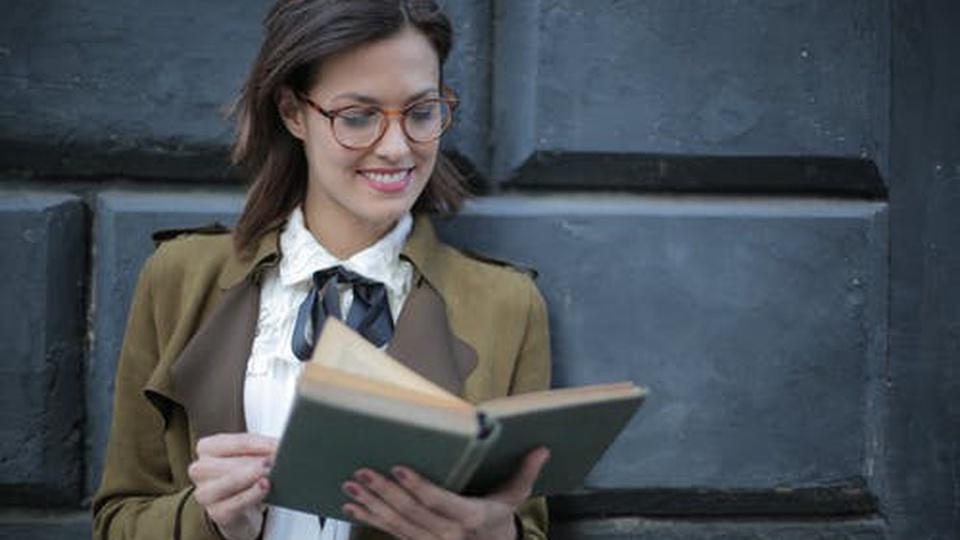 Prefeitura de Presidente Epitácio: mulher sorridente olhando para livro