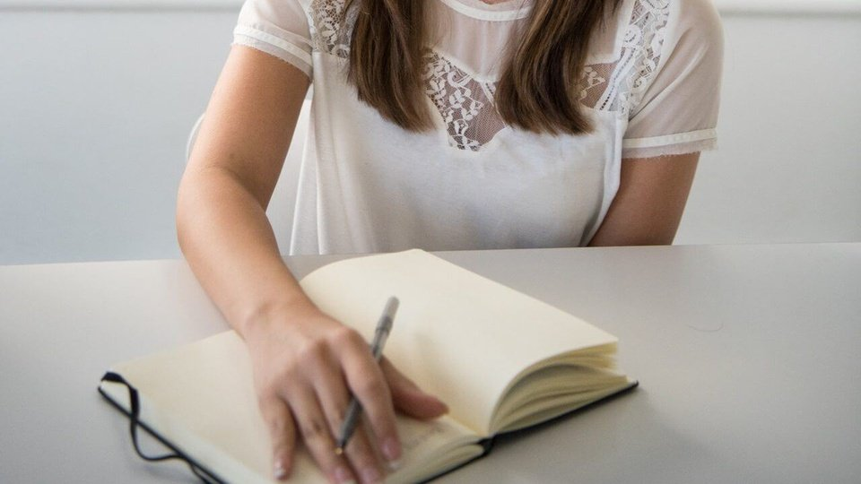 Concurso Prefeitura de Osasco: a imagem mostra pessoa segurando lápis com mão posicionada sobre caderno como se fosse fazer uma anotação