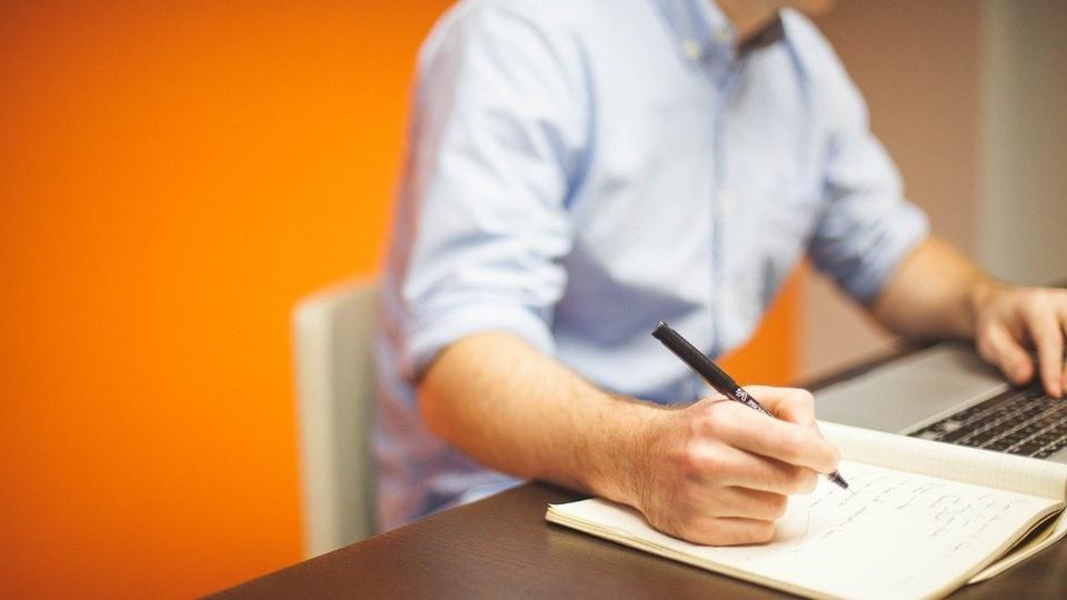 Processo seletivo Prefeitura de Rio Branco - AC: homem sentado escreve em caderno com uma mão e digita em notebook com a outra mão