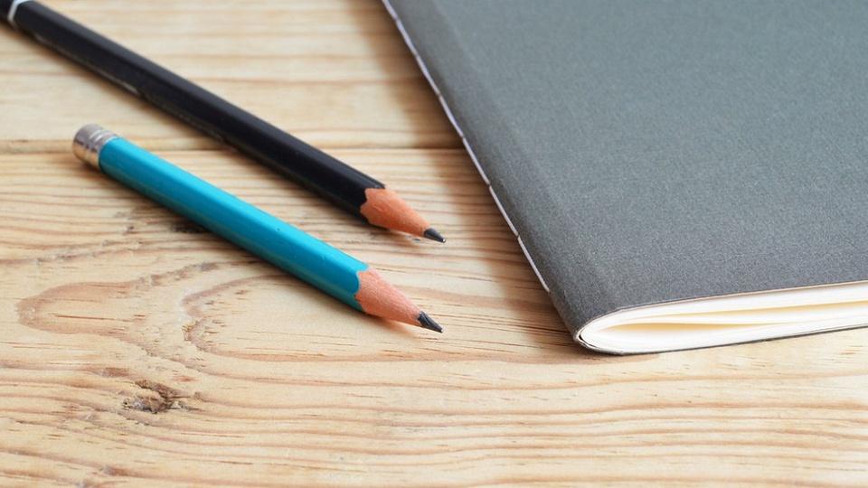Prefeitura de Rolândia: imagem de dois lápis apontados ao lado de um caderninho de brochura fechado