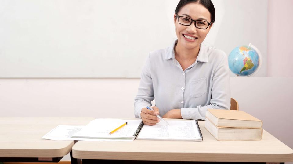 Prefeitura de Salete: mulher de óculos e camisa social segurando uma caneta e sentada à mesa onde há livros e um caderno aberto e com caneta na mão direita; provavelmente professora.